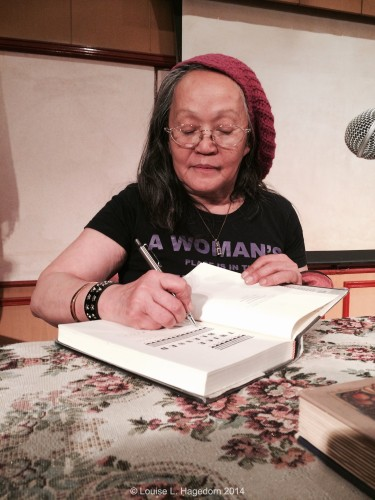 Signing books brought by Ninotchka Rosca's fans.